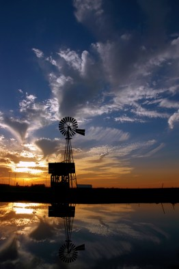 Ranch Windmill Reflected in Farm Pond, Silhouetted Against Dramatic Sunset
