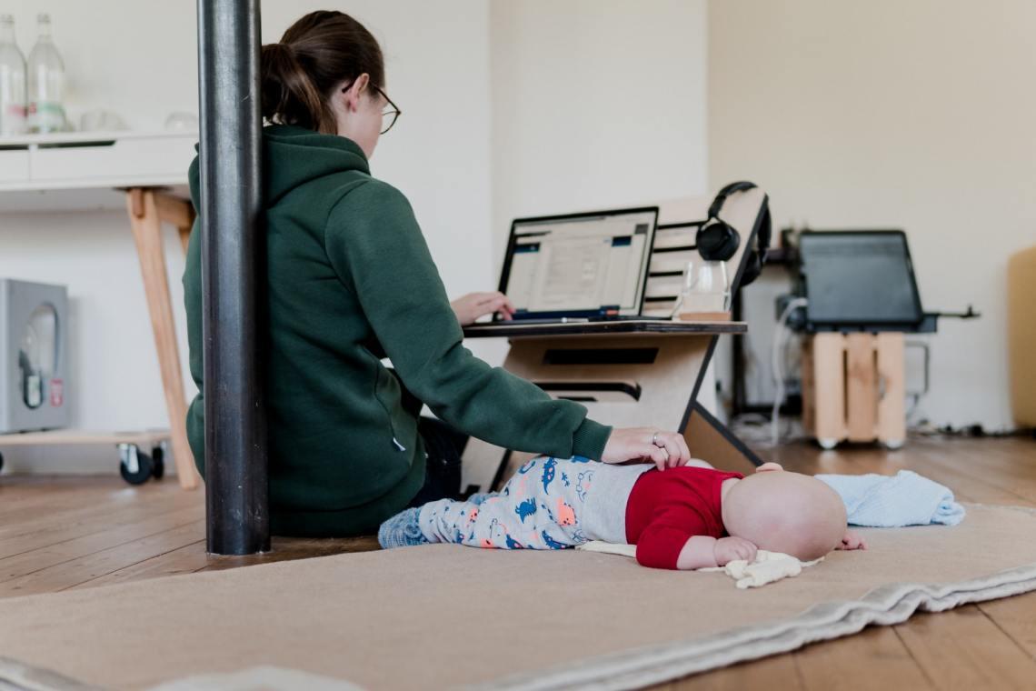 Langzeitstillende Mutter mit Kind bei der Arbeit