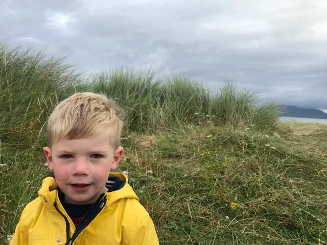Child on machair with rain clouds behind
