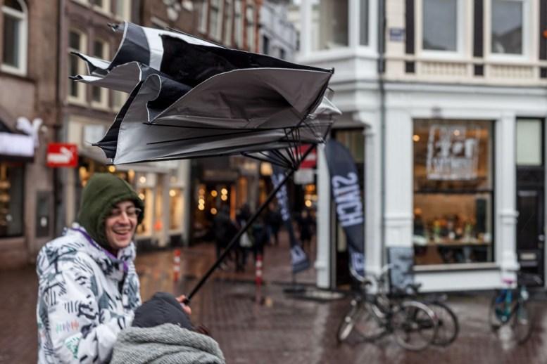 Amsterdam: slecht weer, en dus loopt iedereen met een paraplu of regenponcho. En als het dan ook nog eens hard waait, dan gaan er paraplu's de lucht in.
