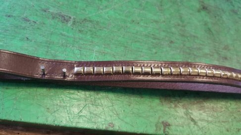 Clenchers fixed to the browband, just pinning the backing piece of leather for comfort.