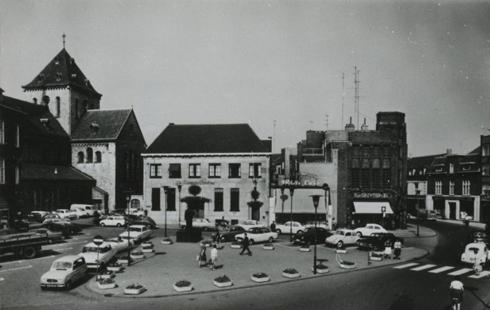Bron: Rijckheyt.nl | Van links naar rechts: St.Pancratiuskerk, Twentsche Bank, reisbureau White Cars, De Gruyter en de Emmastraat. Op het plein het standbeeld van dr.H.Poels.