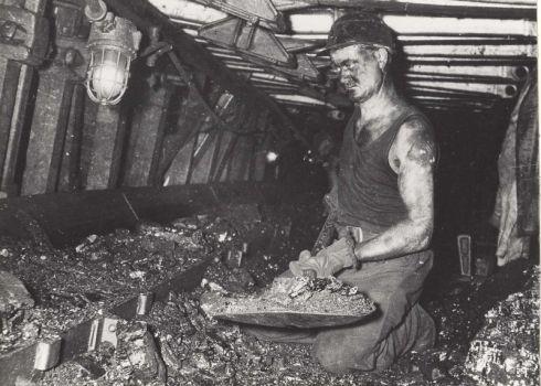 Bron: Rijckheyt.nl | De komst van de gaskachel betekende ook het begin van het einde voor de mijnbouw in Limburg. Foto: Het wegscheppen van losgemaakte kolen in de Beierkettingtransporteur (ook wel schraper genoemd) in een pijler van de Oranje-Nassaumijn I. De mijnwerker is Bertus van Os uit Voerendaal.