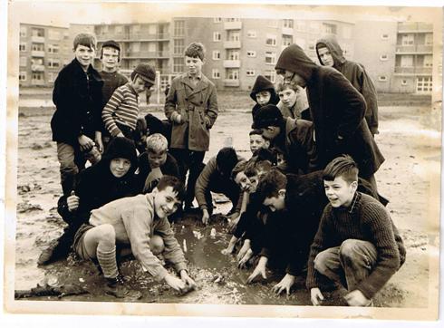 Bron: Collectie Silvio Comis | spelen achter de Pius-X | Silvio Comis staant in het midden. Met streeptruitjeen pet met kleppen; Heintje Zweiphennig, muts met bril; Johny Ploum, op voorgrond links; Huub Hollands, met bontkraag aan rechterzijde Alex Italiaander (marktkoopman) en overig nog Leo Giebels, Ronnie Böhmer