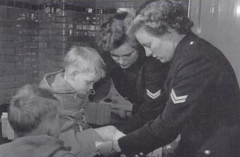 Bron: Collectie Spaarnestad Fotoarchief/NFGC | Taak van de Vrouwelijke Politie: eerste hulp bij ongelukken, heerlen 1953. De kinderenzijn zoontjes van hoofdinspecteur Prick
