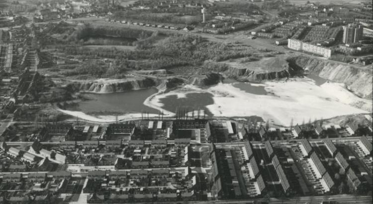Bron: Rijckheyt.nl | Luchtfoto van Heerlerheide. In het midden een zilverzandgroeve. Op de achtergrond Vrieheide. Op de voorgrond de Maria-Christinawijk in Heksenberg.