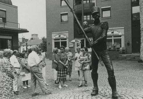 Bron: Rijckheyt.nl | Stadswandeling onder leiding van een gids van de VVV. Rechts het beeld van 'der Koehp va Hehle', gemaakt door mevr. Vera Tummers-van Hasselt.