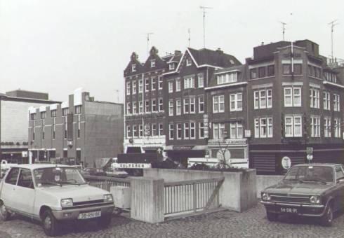 Bron: Rijckheyt.nl | Bongerd. Op de voorgrond het hekwerk boven de ingang van de rijwielstalling. Op de achtergrond van rechts naar links: juwelier Vaessen, reisbureau Neckermann, gordijnenhuis P.Käller, café De Tapperij, café De Kruik, modemagazijn Kreymborg en warenhuis Vroom & Dreesmann (1979)