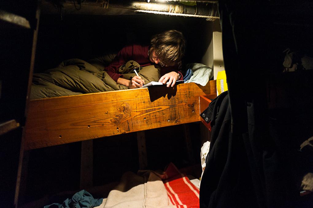 Marteen rédige son carnet de bord dans sa couchette à l'avant du navire.
