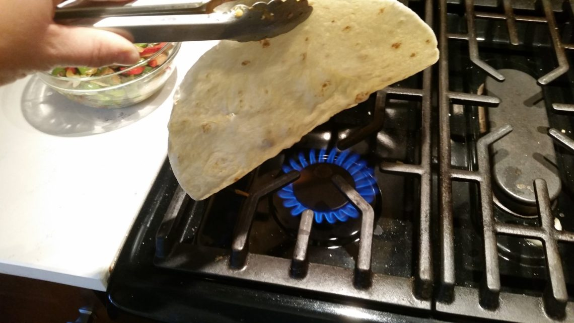warming a tortilla for a chicken fajita roll up