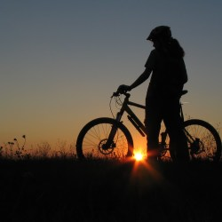 girl stands with bicycle as sun sets