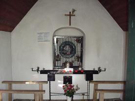 Achtergevel met het hoofd van Sint Jan de Doper en het offeraltaar. Links ziet u het tekstbord van het Gilde St. Jan