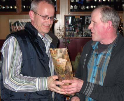 foto Bennie v Hooff Erik (links) ontvangt uit handen van onze voorzitter Janus van Hooff een cadeaubon en een fles wijn.