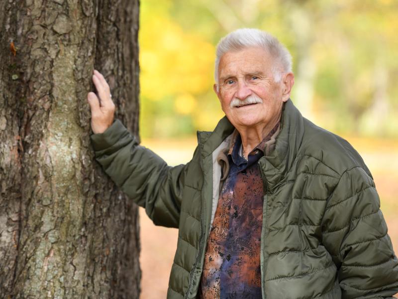 An elderly man leans his hand against a tree.