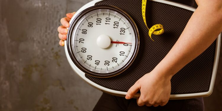 Woman with bathroom scales and a tape measure