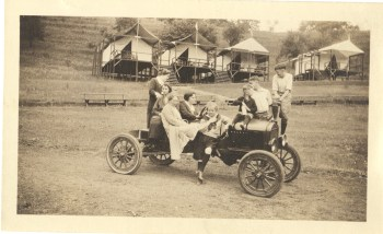 Kids and adults pile on a vintage car in front of a row of tents on platforms, c. 1920. General Photograph Collection, Detre Library & Archives at the History Center.