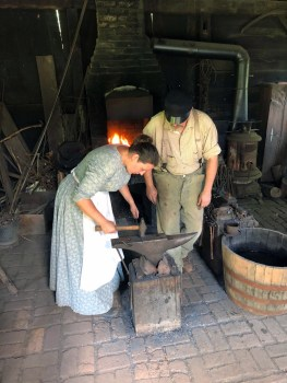 Sarah Kizina on her first day working in Meadowcroft's blacksmith shop. Dewayne Curry, the primary smith at Meadowcroft, is teaching.
