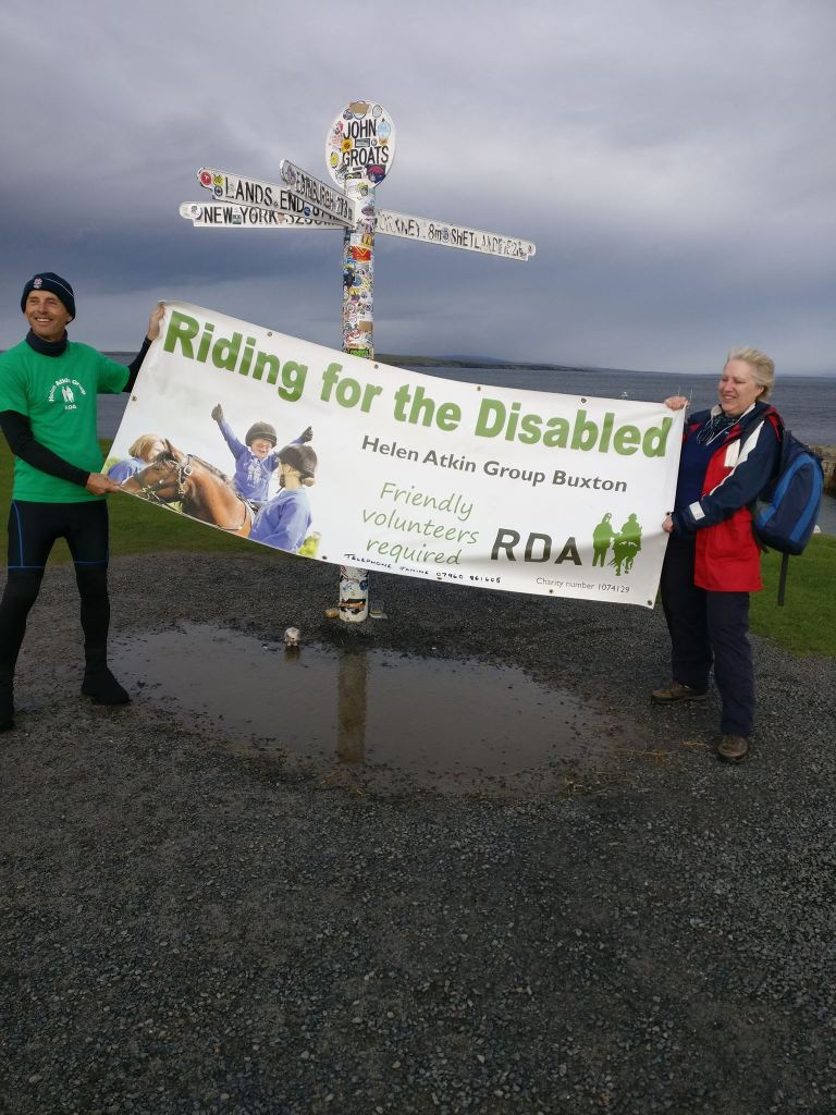 Two people holding a sponsored walk banner