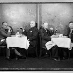 ©©Ken Shung - Four Men at Geno's. Black and white-men at dining tables, looking at the camera, restaurant, NYC