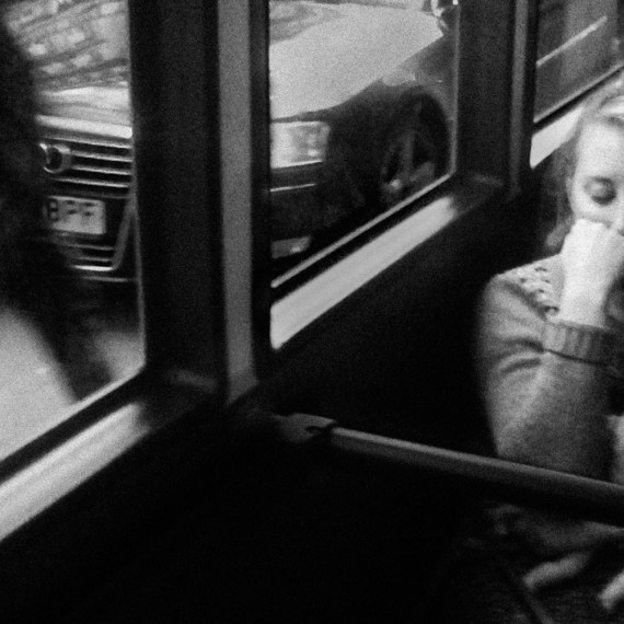©Robert Goldstein 'London Bus'- black & white. Woman on a bus holding a baby doll