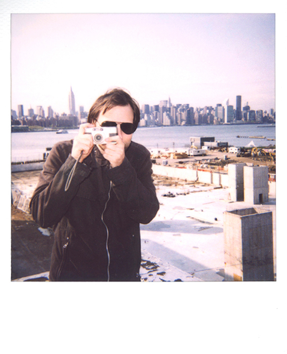 Photographer, Oskar Landi, Bio pic - Landi points a camera at the photographer, with Manhattan in the background