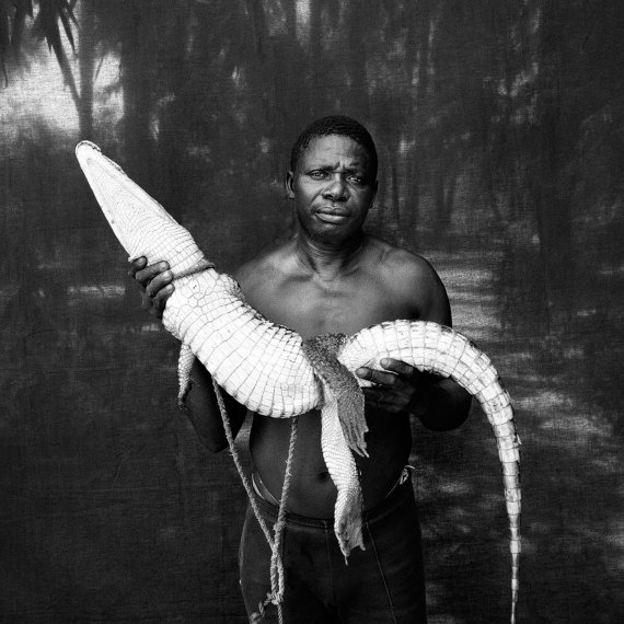 ©©Jason Florio -Abdou with Rescued Crocodile, The Gambia, West Africa.BW portrait from Makasutu series, against black cloth background
