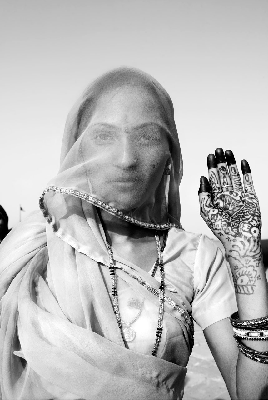 Jason Florio photography - Black & White image of a beautiful woman, Indian bride, in a sari and veil, looking at the camera, holding up her hennaed hand