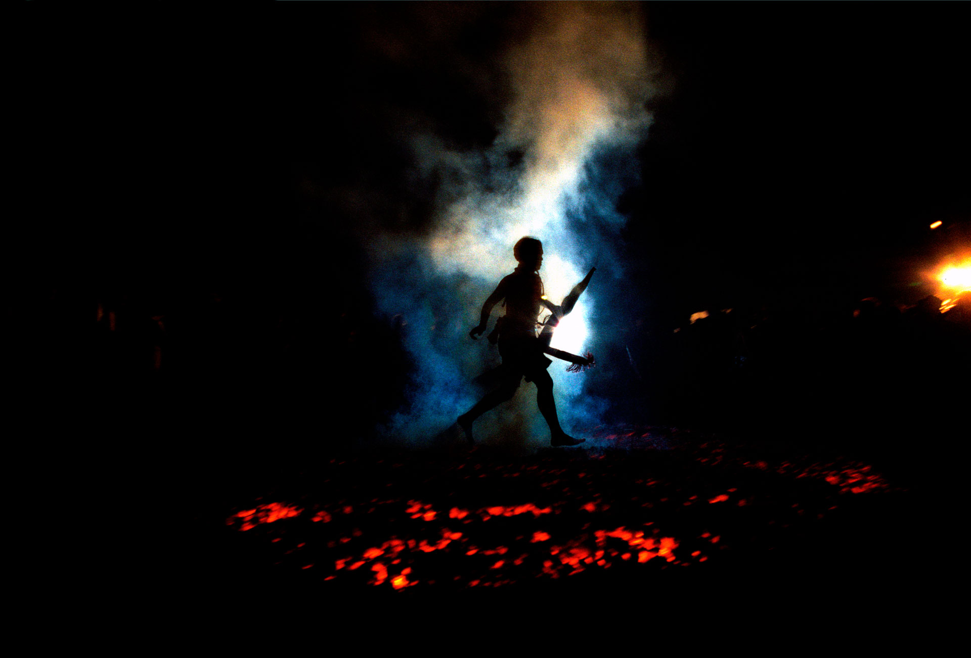 Jason Florio photography - color image a man, firewalker, walking across hot coals at a ceremony in Thailand