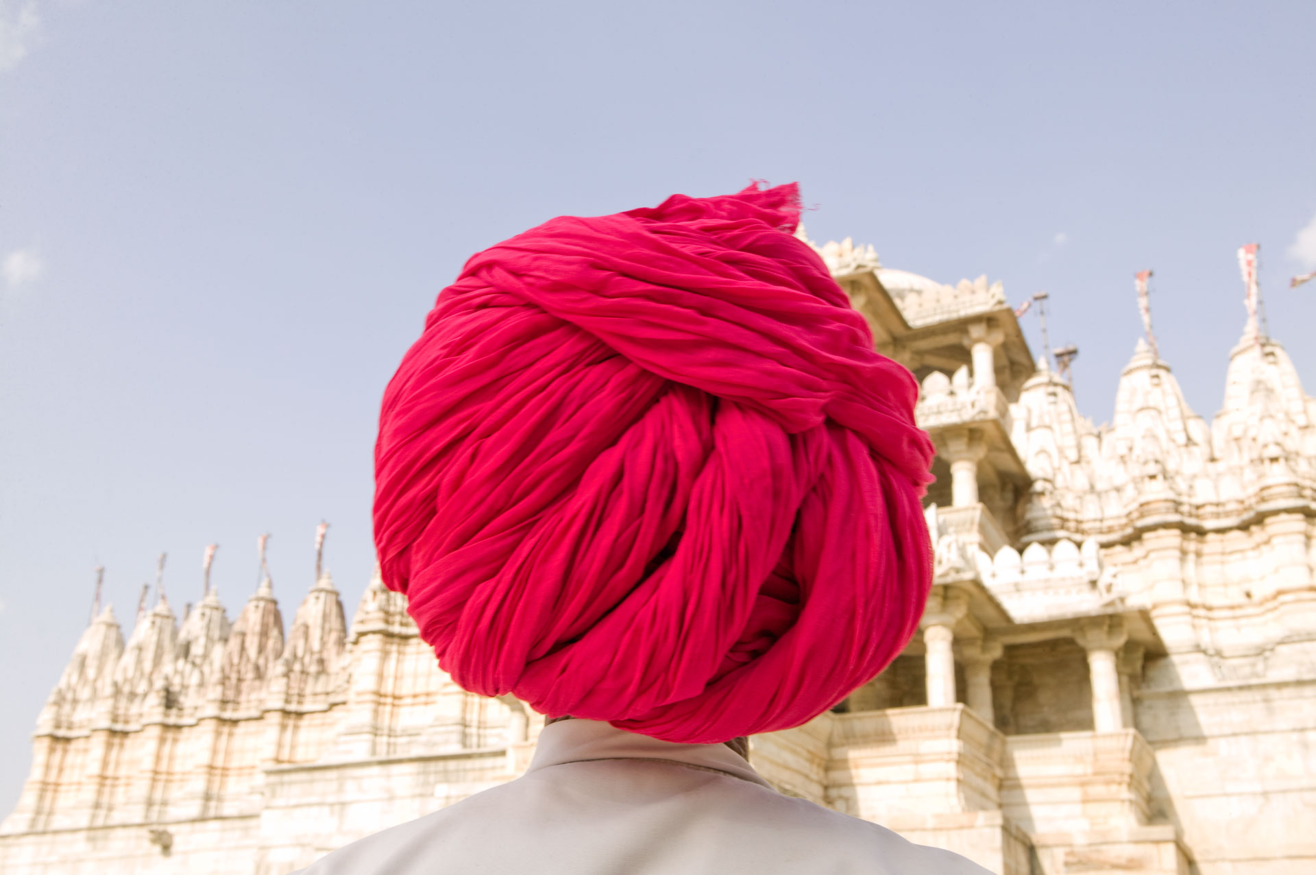 Jason Florio photography - color image a man in a vibrant pink/fuchsia tuban, with his back to the camera, looking at a temple, India