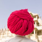 ©Jason Florio - 'Fuchsia Turban, India' - color man in a vibrant pink turban, with his back to the camera, looking at a temple