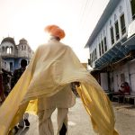 Pushkar Man Walking, India ©Jason Florio - color image of a turbaned Indian man walking away from the camera, in yellow robes