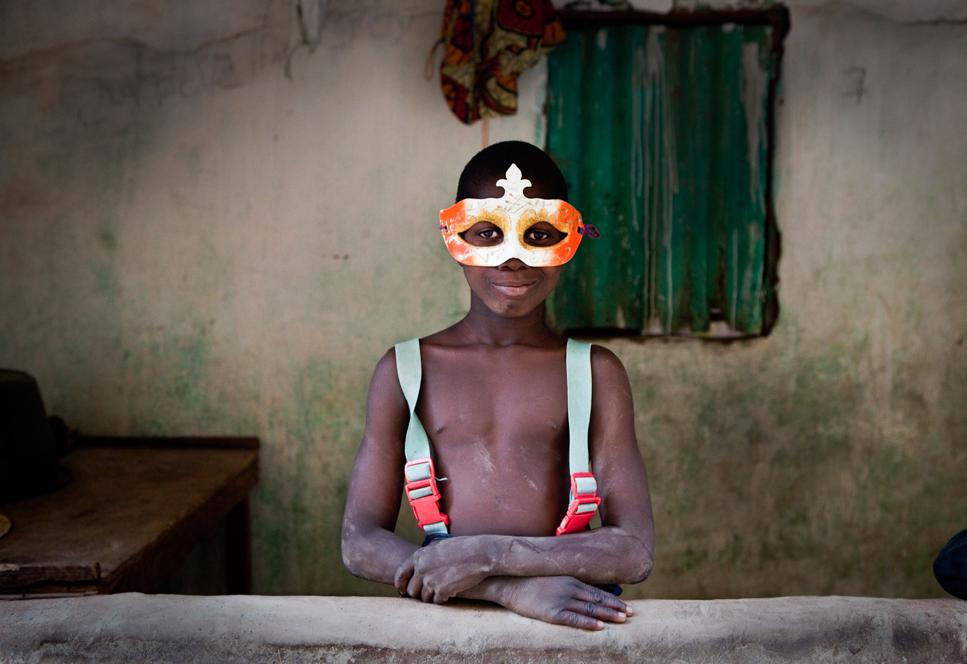 JASON FLORIO photography - color image of A YOUNG GAMBIAN BOY, WEARing A PARTY MASK, STARING AT THE CAMERA,THE GAMBIA, WEST AFRICA