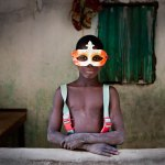 BOY IN THE MASK © JASON FLORIO. Color - portrait of young Gambian boy wearing a mardi gras mask and braces