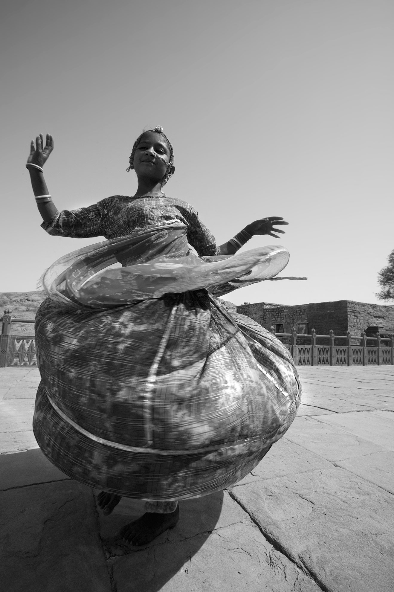 Jason Florio photography - black and white image of a young Indian Girl, dressed for a celebration, spins around in her long dress, billowing out, India