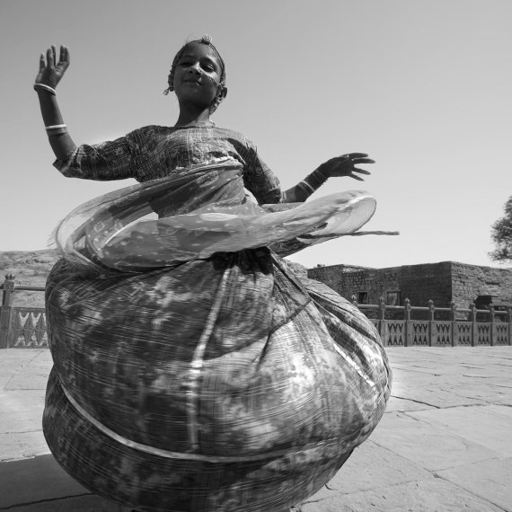 Indian Girl Dancing - India © Jason Florio. BW young girl twirls around in her long dress