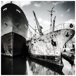 RELICS © Helen Jones-Florio. Black and white-rusty boats in shipyard, Malta