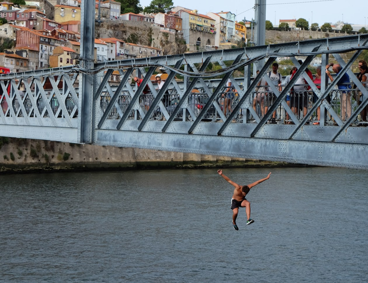 A young lad jumps into the Douro river from the Luís I Bridge