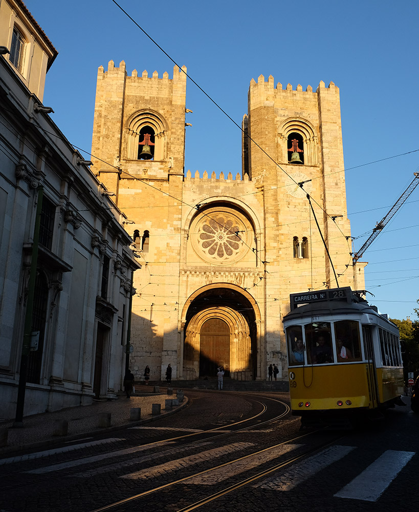 One of Lisbon's famous yellow trams in front of the lovely cathedral