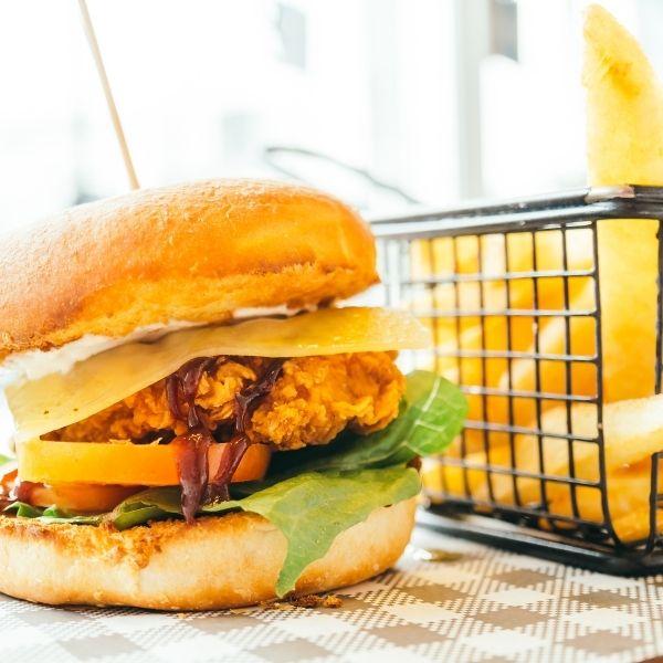 Burger s obaľovanými kuracími prsiami, cheddar syrom, slaninou, paradajkami, šalátom, BBQ dressingom a zemiakovými rúrkami.