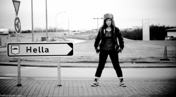 A photograph of Grace standing next to a street sign in Hella, Iceland.
