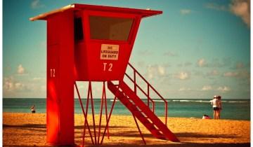 A red lifeguard tower on the sands of world famous Waikiki Beach, Oahu, Hawaii.