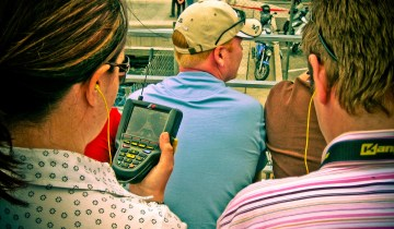 Spectators plug into an audio and video feed of the race via a portable Kangaroo TV (now Fanvision) unit.
