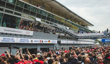 A crowd of Formula One fans jockey for a view of the Ferrari garage.