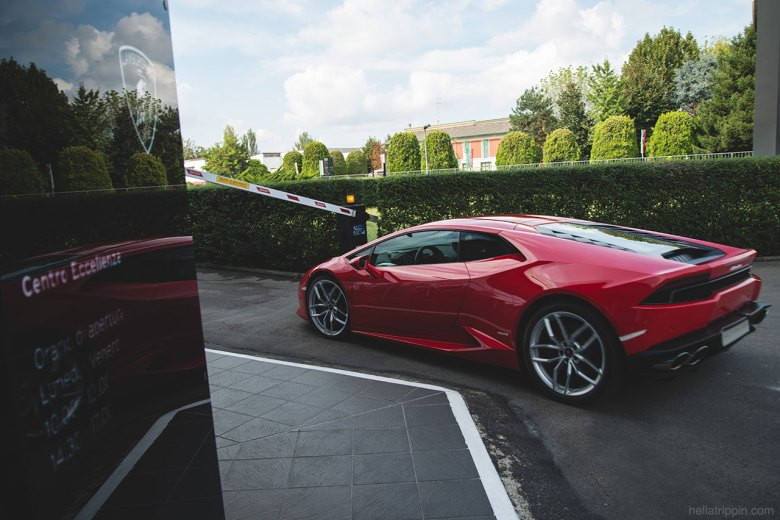 A red Lamborghini Huracán cruises through the parking lot of the company headquarters in Sant'Agata Bolognese, Italy.