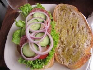 Sandwich med olivenolje, aioli, tomat, salat, løk, agurk, manchegoost og italiensk salami.
