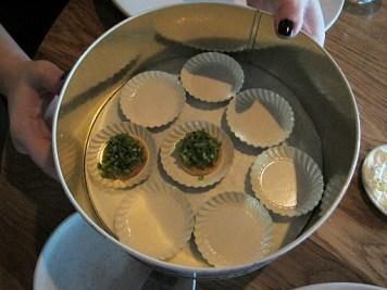 Kakeboks med små kjeks med hakkede urter og kremost.
