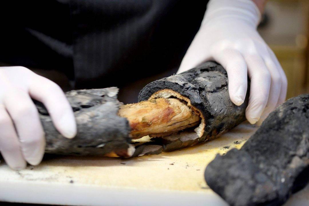 """Skallet på de sorte """"brødene"""" kakkes løk og svinefiletene dukker frem."""
