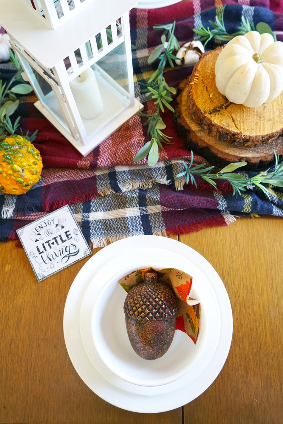 DIY Fall Tablescape with white Corelle Dinnerware, plaid blanket, wood accents, and fall pumpkins.