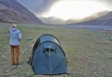 Wanderin vor ihrem Zelt bei Sonnenuntergang