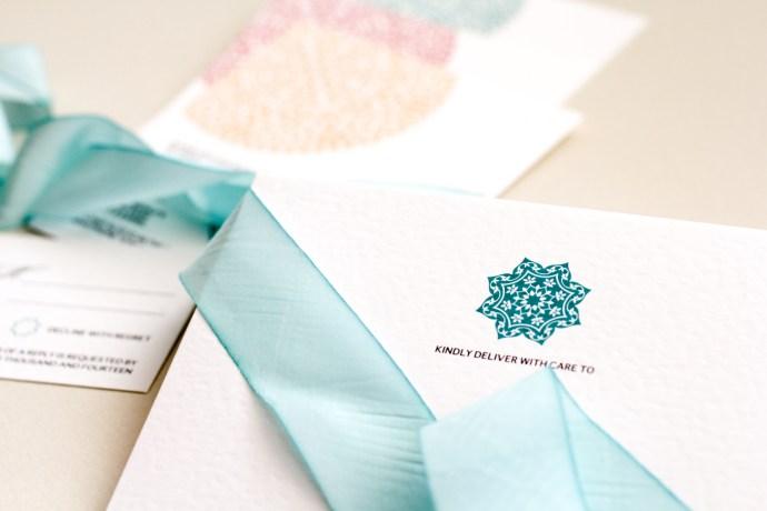 modern rosette in teal on white cotton paper invitation